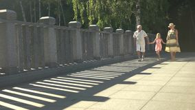 Child with grandparents walking on bridge. Senior man and woman holding hands with granddaughter and walking, sunny summer day stock video
