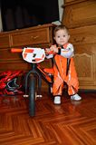Child grasps steering wheel balance bike is worth. A child in the orange jumpsuit while standing holding the handlebars the small balance bike Stock Image