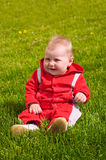 Child on a grass. Infant in red clothes sitting in the middle of green grass. He is smiling Royalty Free Stock Photos