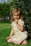 The child on grass. The little blonde girl sitting on the grass stock images
