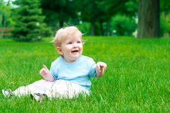 Child on the grass. Happy little boy on green grass in summer Stock Image