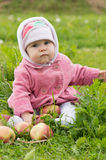 Child in the grass with apples Royalty Free Stock Photos