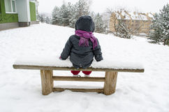 Child with gray jacket sitting on bench in winter Stock Images