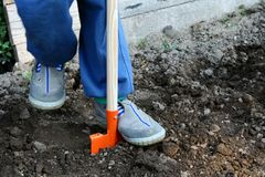 Child in gray shoes cultivating soil with orange toy spade. Child in blue jeans and gray shoes cultivating soil in garden with orange steel toy spade. Concrete stock photography