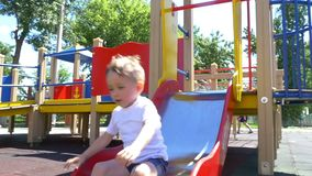 A child with a great pleasure rides a slide on a playground in a slow pace. Slow motion stock video footage