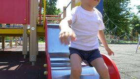 A child with great pleasure, riding a slide on the playground in a slow motion. Slow motion stock video