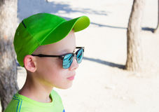 The child in a green baseball cap and sunglasses. Near trees Stock Photo