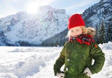Child in green coat standing in the front of snowy mountains Stock Image