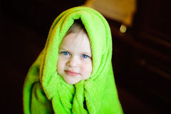 Child with green fleece blanket on his head on a dark background Royalty Free Stock Photo