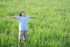 Child on green natural meadow. Kid on meadow, happy and free stock photography