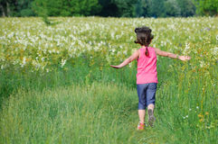 Child on green spring meadow, kid running and having fun. Outdoors Royalty Free Stock Image