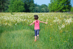 Child on green spring meadow, kid running and having fun. Outdoors Stock Images
