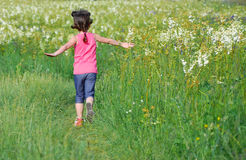 Child on green spring meadow, kid running and having fun. Outdoors Royalty Free Stock Photography