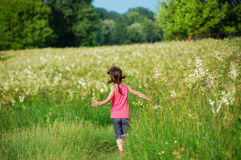 Child on green spring meadow, kid running and having fun. Outdoors Royalty Free Stock Photos