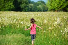 Child on green spring meadow, kid running and having fun. Outdoors Royalty Free Stock Images