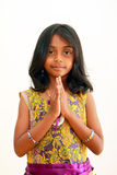 Child greeting with a traditional indian welcome. Asian Indian girl greeting in a tradtional Indian welcome, namaste, with a smile royalty free stock image