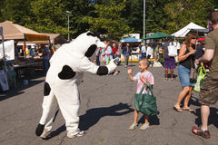 Child Greets Costumed Cow Character. At a public farmer's market in Reston, Virginia, this young child was delighted to greet a costumed cow figure with a big Stock Photo