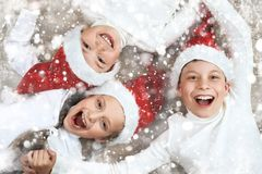 Child group lying together on wooden background and laugh, dressed in christmas Santa hat and having fun, winter holiday concept,. Snow decoration Stock Photos