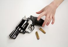 Child Gun. Child's hand reaching for a handgun and bullets on white background Stock Photo