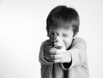 Child with gun on light background. Pre-teen boy aiming forward a silver pistol, focus on the foreground, shades of gray, copy space Royalty Free Stock Images