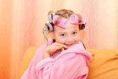 Child  hairdo sitting  orange sofa. Royalty Free Stock Image