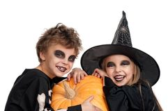 Child in halloween costume. Boy and girl wearing halloween costume with pumpkin on white background Stock Photo
