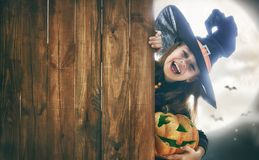 Child on Halloween. Happy Halloween! Cute little witch with pumpkin. Beautiful young child girl in costume on full moon background. Space for text stock image