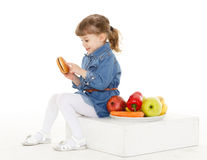 Child with hamburger and fruits. Royalty Free Stock Photography