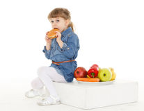 Child with hamburger and fruits. Royalty Free Stock Images