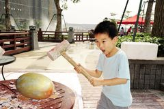 A child hammer a golden egg Stock Image