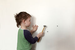 Child hammering plastic anchor Royalty Free Stock Photography