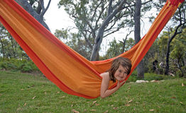Child in hammock. A little girl nestled in a bright orange hammock in the middle of the Australian nature; eucalyptus trees in the background Royalty Free Stock Image