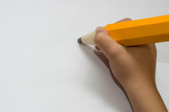Child hand with big orange pencil Royalty Free Stock Photo