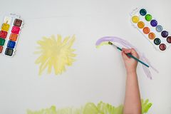 Child hand with brush drawing yellow sun on white paper. Child drawing top view royalty free stock image