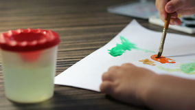 Child hand with brushes drawing on white paper stock video footage
