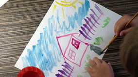 Child hand with brushes drawing on white paper top view stock video footage