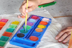 Child hand choose color from watercolor paint pallet Royalty Free Stock Image