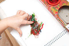 Child hand with colorful finger paints. Colorful finger paints over white background Stock Photos