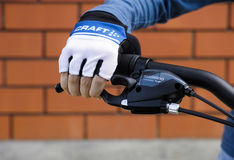 Child hand with Craft glove on handlebars with Shimano brake lev Stock Photos