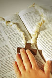 Child hand and cross on the Bible . Small child's hand touching wooden cross on pearl rosary on an open Bible with text of Resurrection in warm afternoon sun Royalty Free Stock Image