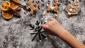Child hand drawing big snowflake in the flour prepared. To make the christmas cookies - with gingerbread figurines on the side stock footage
