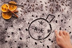 Child hand drawing christmas bauble in flour. Child hand drawing christmas bauble in the flour prepared for the gingerbread cookies, shallow depth royalty free stock photo