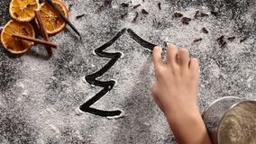 Child hand drawing a christmas tree in the flour