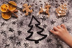 Child hand drawing holidays scene in the flour prepared for the. Child hand drawing holidays scene with xmas tree and stars in the flour prepared for the Stock Photos