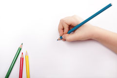 Child hand draws a blue pencil. 