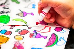 Child hand with felt-tip pen drawing small pictures on paper. Child hand with red felt-tip pen drawing small pictures on paper stock photography