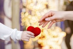 A child hand is giving a small heart to the adult hand royalty free stock images