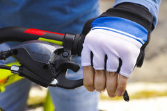 Child hand with glove on handlebars with brake lever. Close-up Stock Image