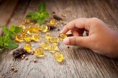 Child hand hold Cod liver oil omega 3 gel capsules Stock Image