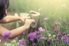 Child hand holding bamboo railing in the flower garden Royalty Free Stock Images
